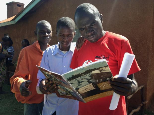 Youth receive the Resource Guide that accompanies the film 'An African Answer'