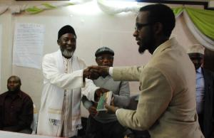 Abdi Yarow, Centre for Ihsan Education and Development, receives an Arabic DVD of 'The Imam and the Pasto' from Imam Muhammad Ashafa and Pastor James Wuye (Photo: Alan Channer)