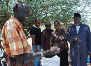 Joseph Kwopin with grass seed. Imam Muhammad Ashafa looks on. (Photo: Alan Channer)
